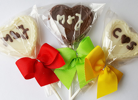 two white heart shaped chocolate lollipops on each side with one dark heart shaped chocolate on the center